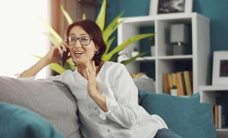 Portrait of cheerful adult woman talking on smartphone sitting sideways on couch in flat