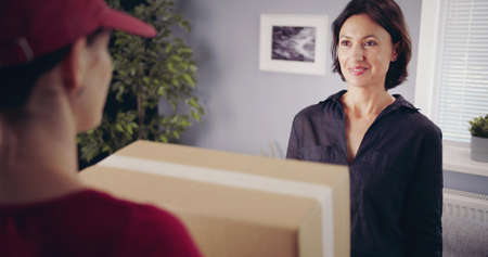 Smiling brunette looking at deliveryman who holds carton box, rear view of courier