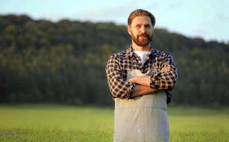 Happy male agrarian with arms folded standing on green field looking at camera, half-body portrait
