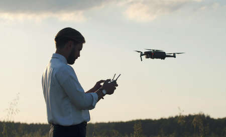 Side view of man holding remote controller navigating quadcopter hovering in air, half-length shot