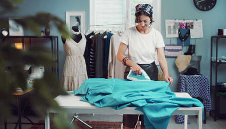 Positive woman ironing fabric preparing for sewing while working in fashion clothing studio Banque d'images
