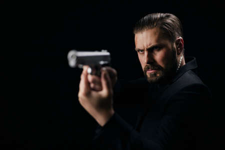 Serious bearded man aiming with gun over black background. Criminalist in black suit holding weapon in studio. Crime concept.
