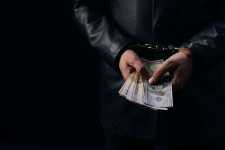 Close up of male hands in handcuffs holding money cash. Arrested person with dollars over black background. Criminal concept.