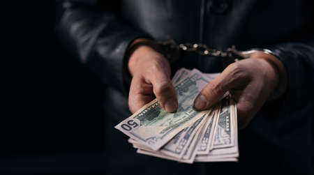 Man in black suit holding dollar banknotes with handcuffs on hands. Isolated over black studio background. Punishments because of corruption.