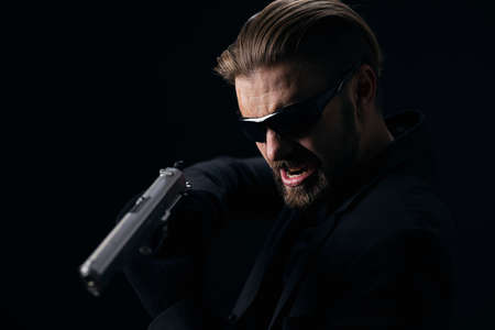 Aggressive bearded man in glasses, suit and gloves threatening someone with real gun. Isolated over black background. Concept of danger.