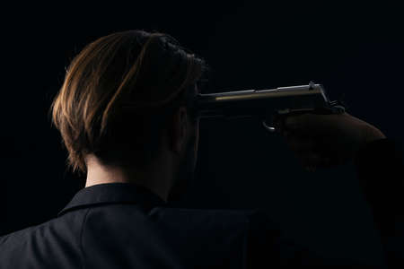 Close up of male hands holding gun near man in black suit. Killer threatening person over black background. Back view of victim.