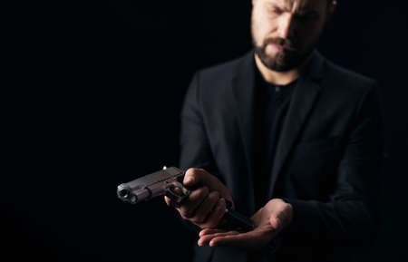 Confident bearded man in black suit holding gun and taking off empty magazine. Serious criminal with weapon over black background. 版權商用圖片