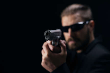 Brutal bearded man in sunglasses and suit aiming with gun over black studio background. Concept of mafia and criminal.