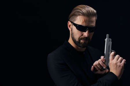Portrait of dangerous gangster in sunglasses holding real weapon while posing in studio with black background. Criminal lifestyle.