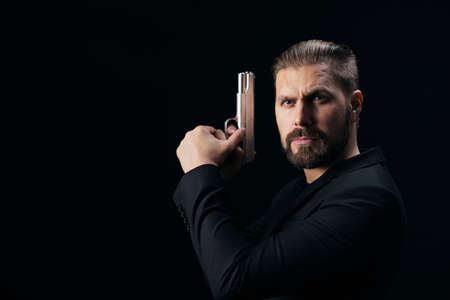 Aggressive bearded bandit in black suit standing over black background with real weapon in hands. Armed person with criminal lifestyle. 版權商用圖片
