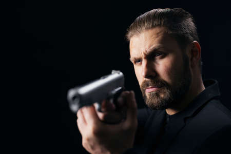 Bearded gangster in suit threatening with gun over black studio background. Confident bandit aiming with weapon. Armed person. 版權商用圖片