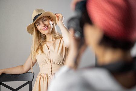 Photographer shooting woman at studio