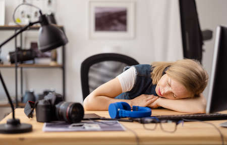 Tired photographer sleeping at office