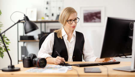 Woman retouching photos at office
