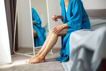 Woman applying cosmetic cream on legs 版權商用圖片