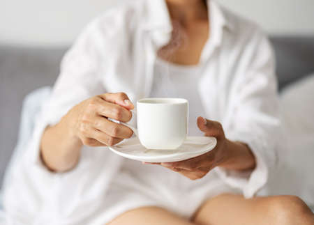 Woman with coffee in bedroom