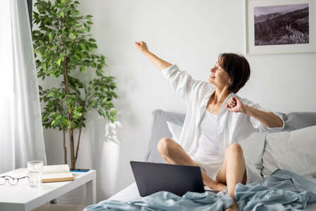 Woman with laptop in bed 版權商用圖片