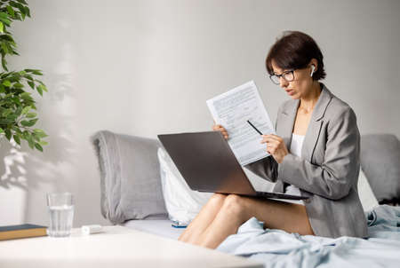 Woman working remotely from bed