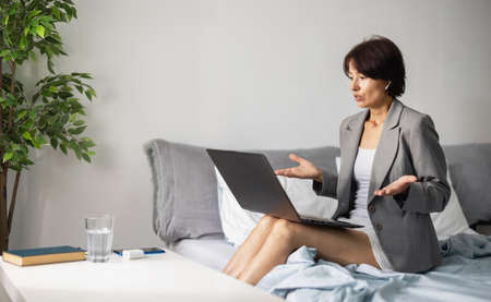 Woman work on laptop in bed 版權商用圖片
