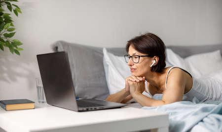 Woman lying on bed with laptop 版權商用圖片