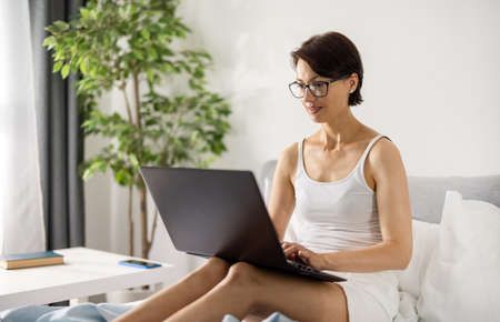 Woman working from bed 版權商用圖片