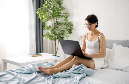 Freelancer with laptop in bed