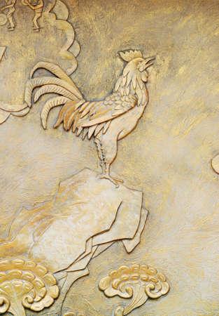 golden relief of rooste on rock Stock Photo - 7808287