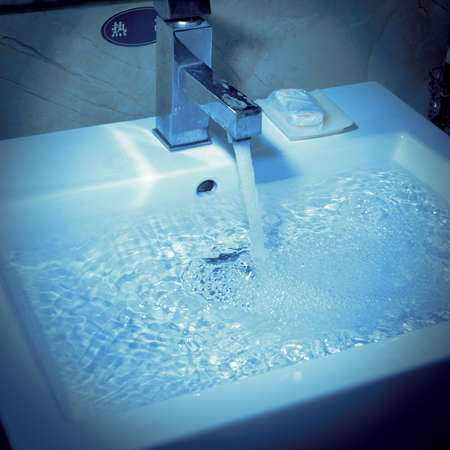 modern wash basin with running water photo