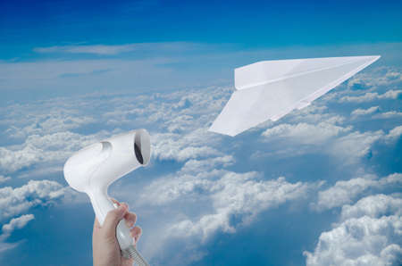 blow drier: blow drier and flying paper plane on  blue sky Stock Photo