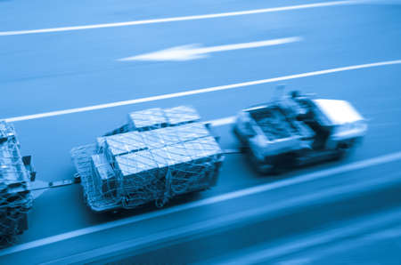 air freight: cargo car delivery on airport blur motion