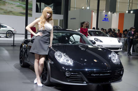 GUANGZHOU, CHINA - NOV 26: unidentified model with Porsche Cayman Black Edition sport car at the 9th China international automobile exhibition. on November 26, 2011 in Guangzhou China.