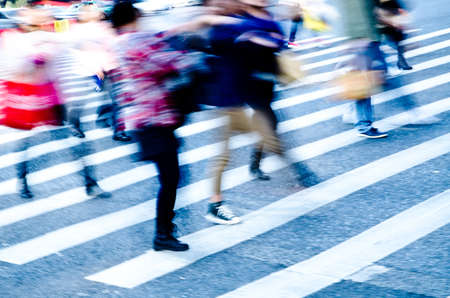 action blur: busy city people crowd on zebra crossing street