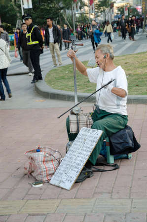 bowed: GUANGZHOU, CHINA - DEC. 04: Unidentified Chinese hand disabled senior man playing a two-stringed bowed instrument and sing on DEC. 04, 2011 in Guangzhou, China.