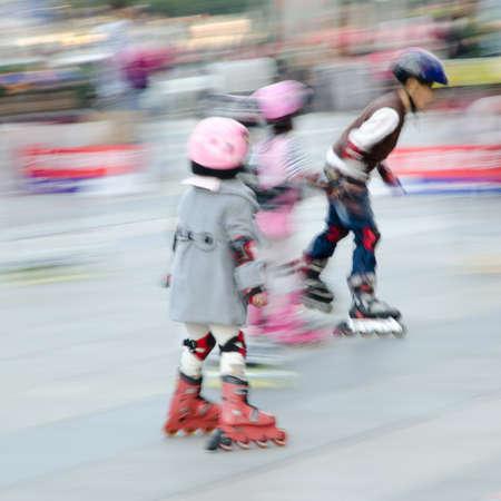 boy skating: child playing rollerblade blur motion Stock Photo