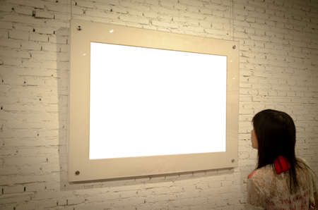 Asian woman looking at picture blank frame on old wall photo