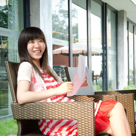 asian woman on chair with paper outdoor photo