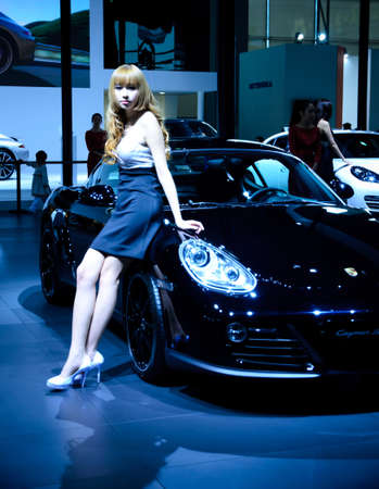 GUANGZHOU, CHINA - NOV 26: unidentified model with Porsche Cayman Black Edition sport car at the 9th China international automobile exhibition. on November 26, 2011 in Guangzhou China. Stock Photo - 13226070
