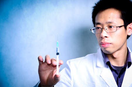 asian men doctor with medical syringe in hand photo