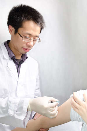 asian doctor injecting vaccination with patient hand photo