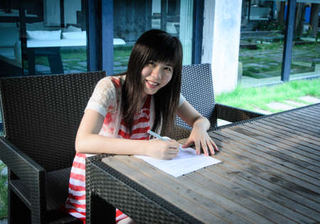 asian woman on desk with paper outdoor photo