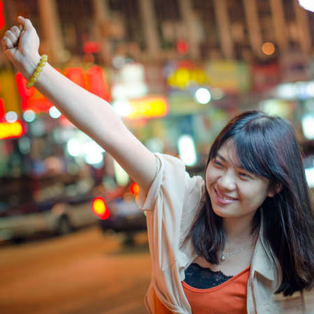Young beautiful smiling Asian woman in street at night photo