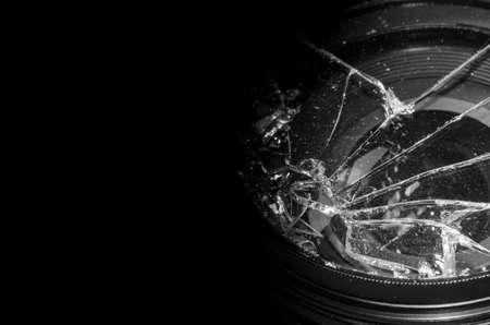 Broken DSLR camera lens on black background