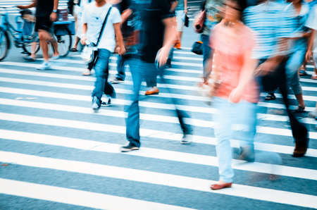people walking on big city street, blurred motion zebra crossing abstract Standard-Bild