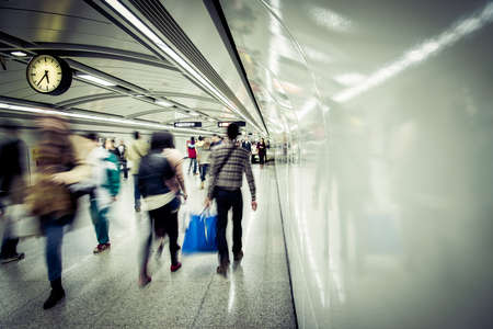 transport interior: business people walk at subway station abstract blur