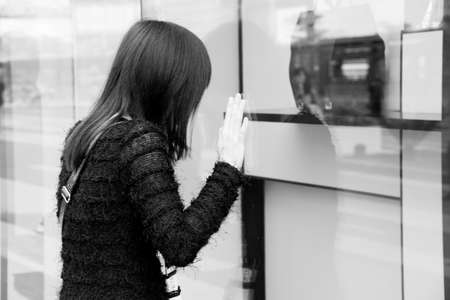 Asian woman looking at urban shop, black and white photo