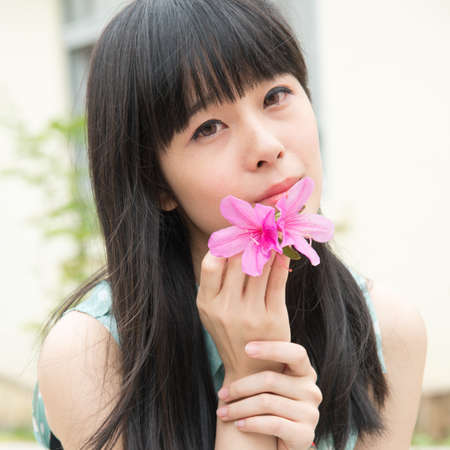 Asian Chinese girl with flower in hand on spring nature day photo