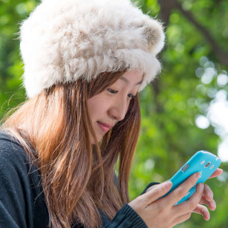 Asian girl using cell phone outdoor photo