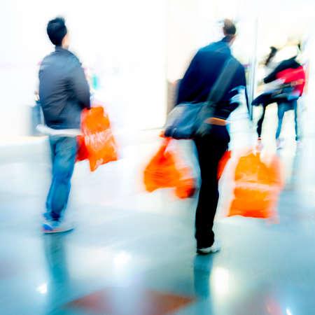 compras compulsivas: la gente de negocios de la ciudad de compras dentro de un centro comercial con la bolsa, el desenfoque de movimiento Foto de archivo