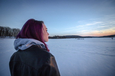 A young woman looking out over a frozen lake at sunset.