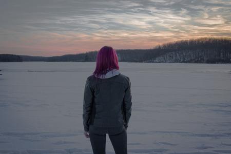 Girl overlooking a frozen lake at sunset. Stok Fotoğraf